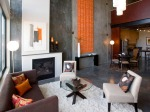 A contemporary living room using orange as accent on gray color paint