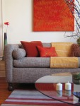 The eclectic coral abstract is just the art needed to lend an unexpected jolt to a tweed sofa in this modern living room